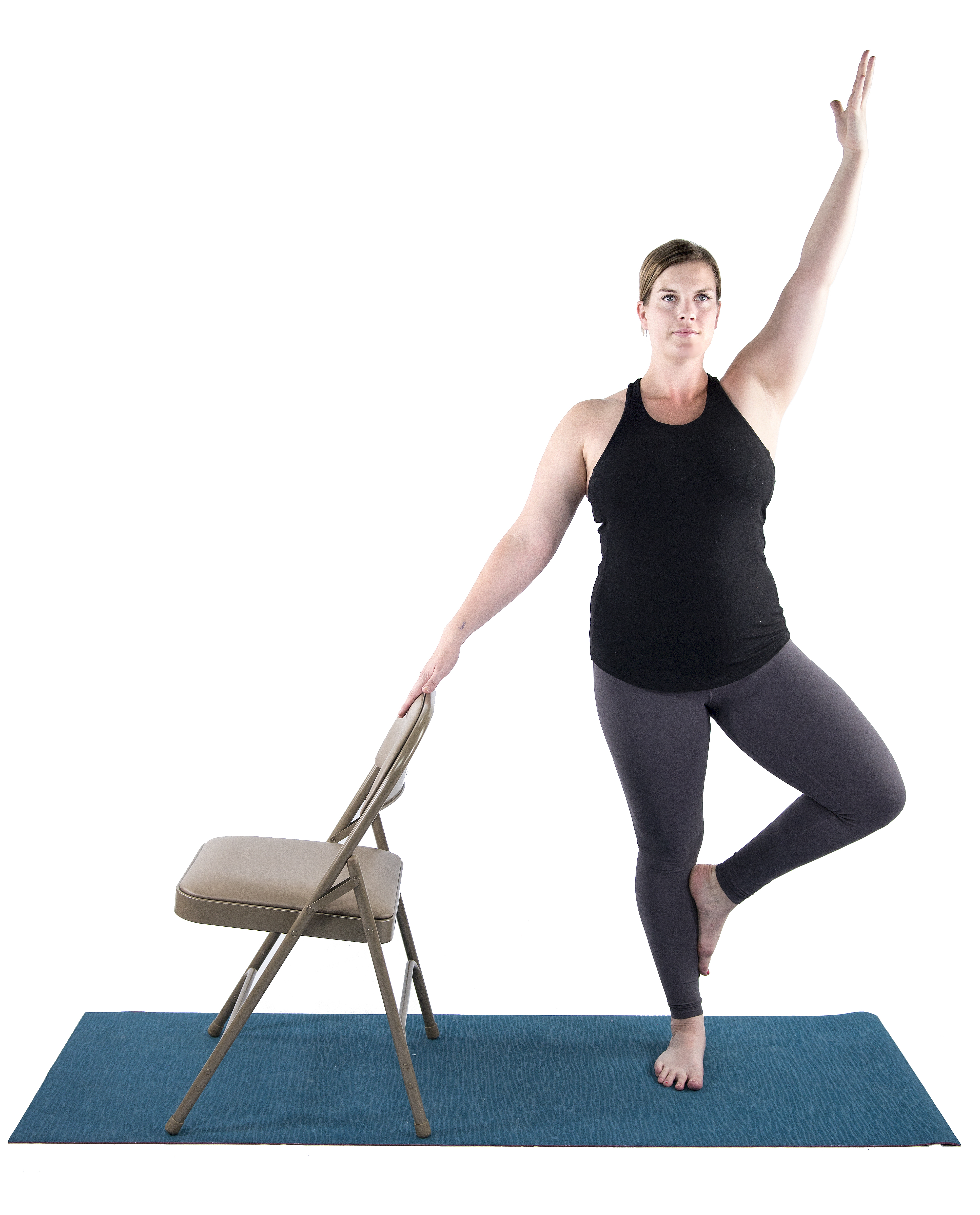woman practicing balancing yoga pose, tree pose, vriksasana, with chair modification for Mulitiple Sclerosis