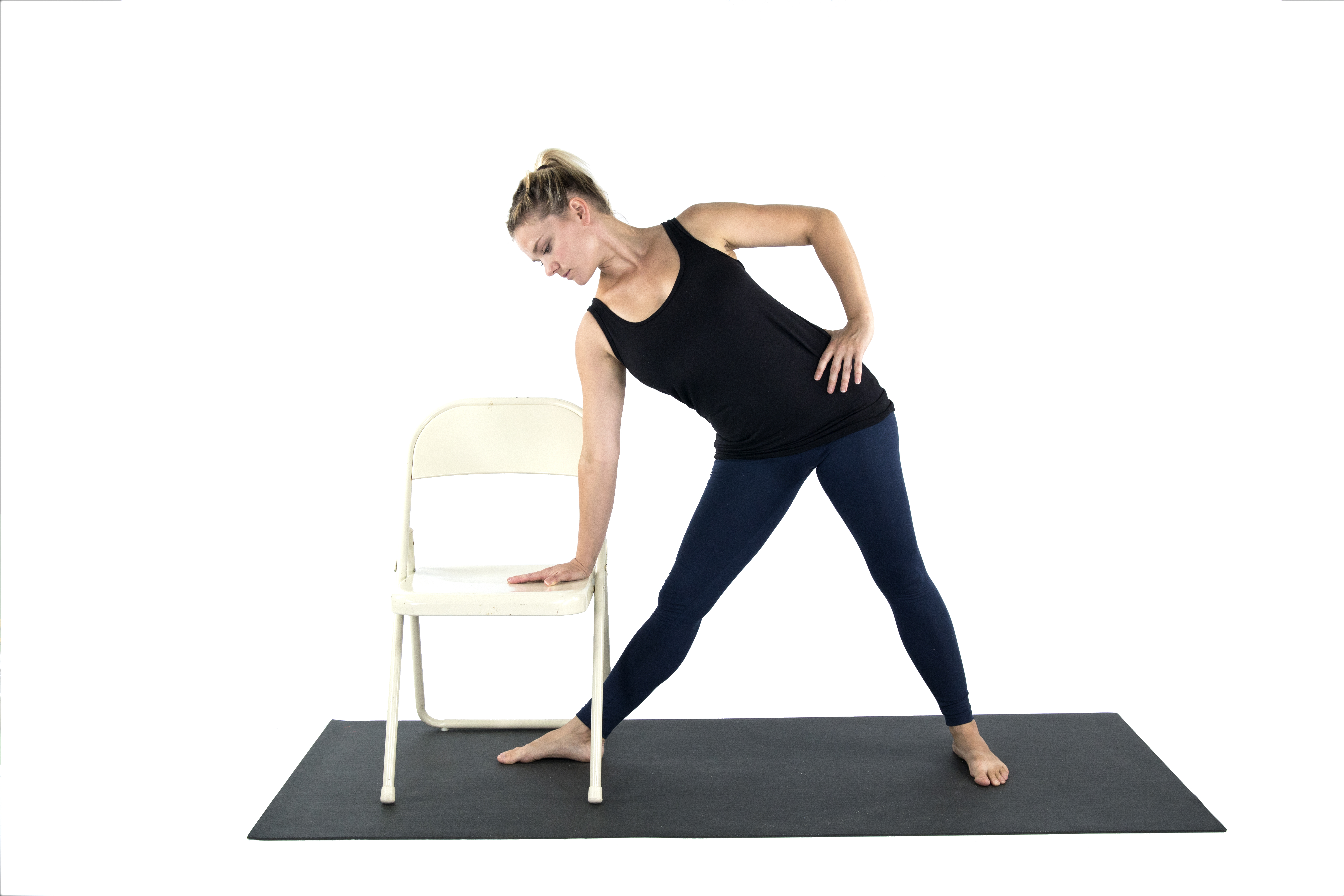 A woman doing a variation of Triangle Pose with the support of a chair in preparation for Warrior 2 yoga pose