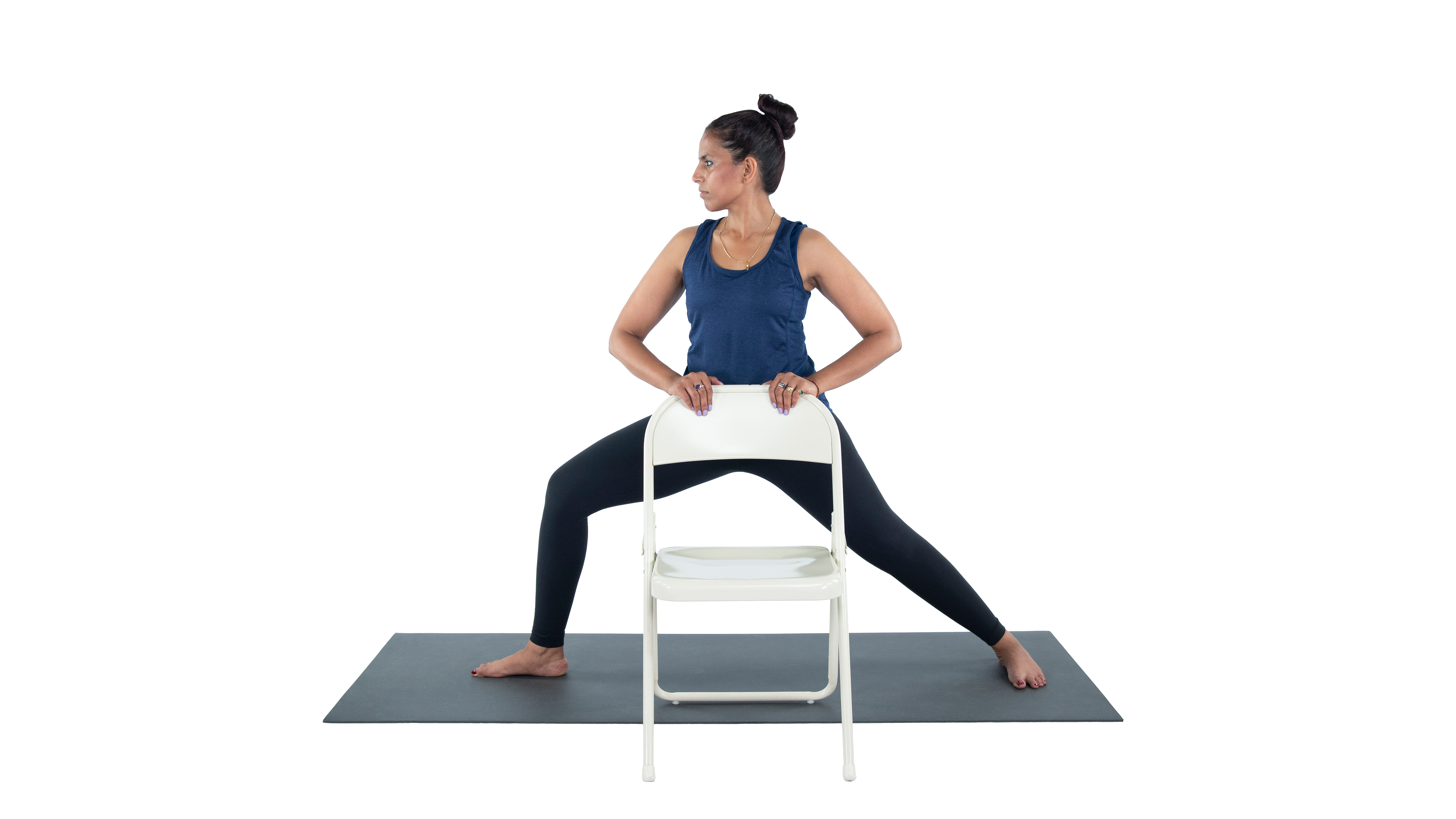 Woman with MS practicing warrior 2 yoga pose (virabhadrasana II) with chair assist for balance