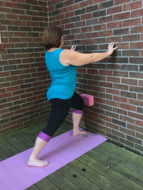 A woman in Warrior 1 yoga pose (Virabhadrasana 1) variation with a block against the wall